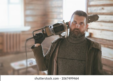 portrait of a adult man with a huge old chain saw on his shoulders in a wooden log hut