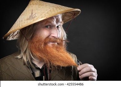 Portrait of an adult man with a red beard and mustache in the Vietnamese hat on a dark background studio