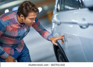Portrait of adult man with scratched car at underground parking lot