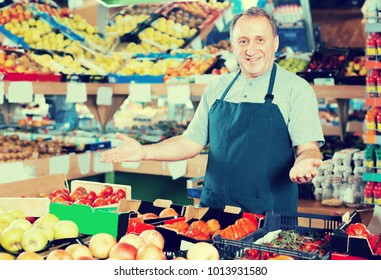 Portrait of adult man seller who is standing on his workplace in supermarket