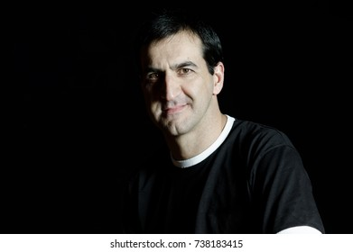 Portrait of adult man with short black hair and black t-shirt on a black backdrop