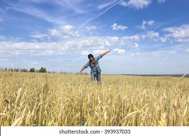 Portrait of an adult man in a wheat field in the aviator image on a sunny day