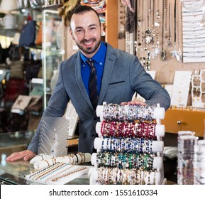 portrait of adult man worker selling bracelets in the jewelry store