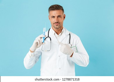 Portrait of adult medical doctor with stethoscope in gloves holding syringe standing isolated over blue background