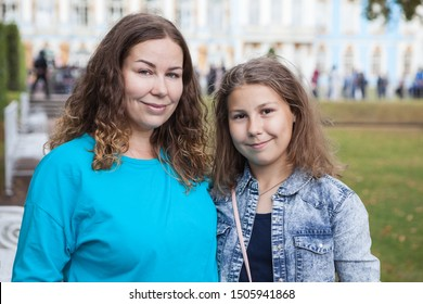 Portrait of adult mother and her preteen daughter, two Caucasian people standing outdoor and looking at camera