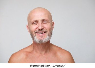 portrait of adult smiling bearded bold skinhead grizzled man  on gray