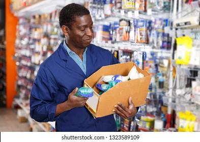Portrait of adult smiling seller of household goods shop organizing assortment of items on shelves and racks