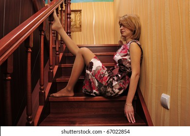 Portrait of adult tired woman sitting on stairs and thinking about something