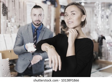 Portrait of adult woman customer trying stylish bracelet in the shop