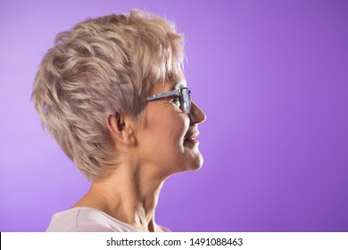 portrait of an adult woman in glasses with a short haircut on purple with a pensive face