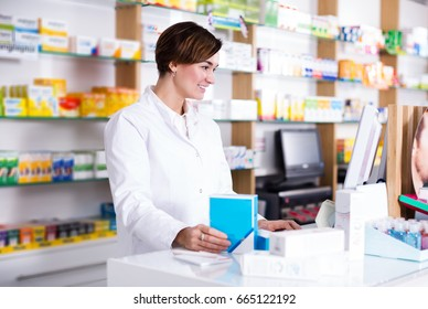 Portrait of adult woman pharmacist ready to assist in choosing at counter in pharmacy