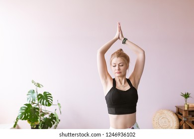 Portrait of adult woman practicing yoga Tree pose Vrikshasana asana indoors, doing yoga and pilates exercise.