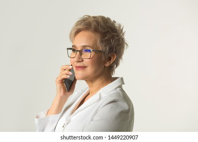 portrait of an adult woman with a short haircut wearing glasses in a white jacket on a white background makes phone calls