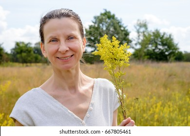 Portrait of an adult woman standing up in a meadow covered with Galium verum flowers, also known as lady's bedstraw or yellow bedstraw, with a bunch of yellow flowers in her hands, in Kiev, Ukraine