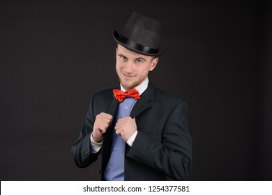 portrait of adult young elegant man in cylinder hat and bowtie on dark background