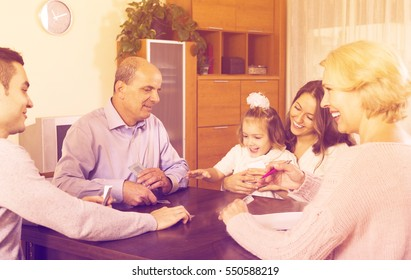 Portrait of adults and little children playing cards together and keeping score