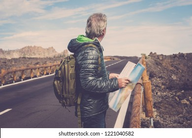 portrait of adventure senior man with map and extreme explorer gear on mountain with long straight road in front of him for a long walk. wanderlust and travel concept image. rocks and sky scenic place