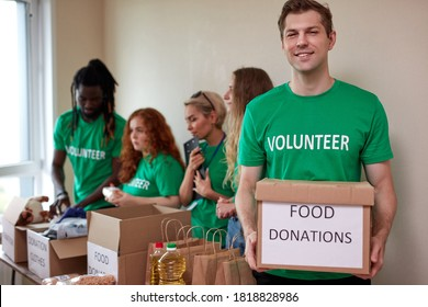 portrait of affable volunteer man in green t-shirt holding donation box in hands while his friends collecting clothes and food in the background