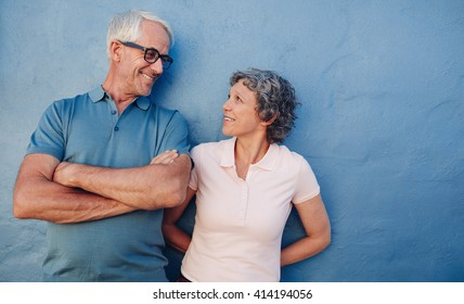 Portrait of affectionate mature couple looking at each other against blue background. Loving middle aged man and woman standing together against a blue wall.
