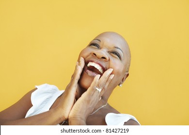 portrait of african 50 years old surprised woman with bald head, smiling on yellow background. Head and shoulders, copy space