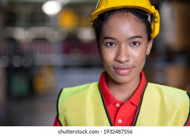 Portrait of African America engineer wearing safety helmet and vest standing in the automotive warehouse with blur background and copy space. Woman looking forward. Distribution and inventory concept