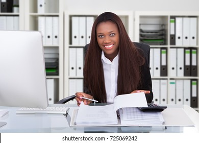 Portrait Of A African American Accountant Woman Calculating Invoice