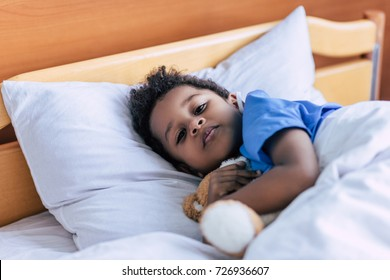 portrait of african american boy hugging teddy bear while lying in bed in clinic