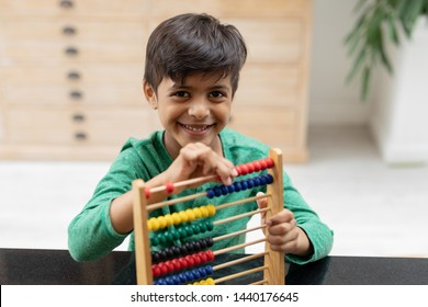 Portrait of African american boy playing with abacus on a table at home