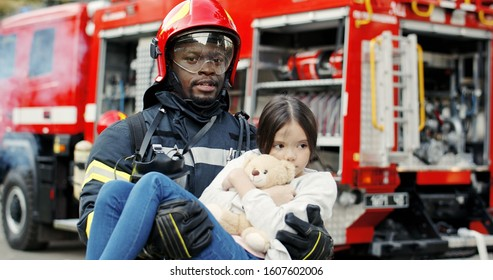 Portrait of african american brave fireman holds saved girl in his arms standing near fire truck. Firefighter in fire fighting operation