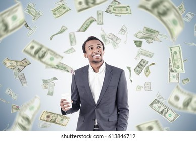Portrait of an African American businessman holding a paper cup of coffee while standing near a gray wall under a dollar rain.