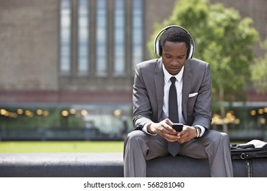Portrait of African American Businessman listening to music with headphones outdoors
