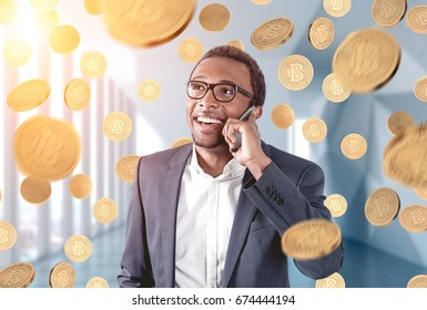 Portrait of an African American businessman wearing glasses and talking on a smartphone and standing in an office under a bitcoin rain.