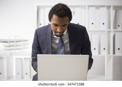 Portrait of an African American businessman working at his laptop with his tongue out. Concept of hard working and perfectionism. Mock up