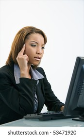 Portrait of African American businesswoman sitting at office desk working on computer.
