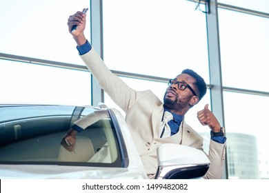 portrait of african american car sales consultant in showroom and making selfie photo on camera smartphone .