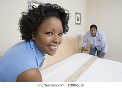 Portrait of an African American couple arranging bed at home