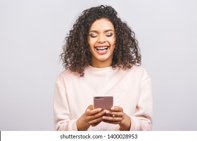 Portrait of african american cute attractive lovely cheerful optimistic wavy-haired girl using new device gadget isolated over white background.