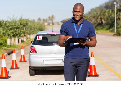 portrait of african american driving instructor writing on clipboard