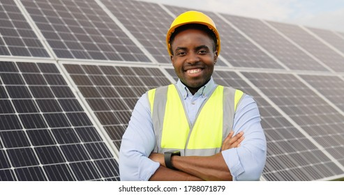 Portrait of african american engineer on background field of photovoltaic solar panels. Black man technician at solar station.
