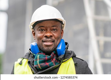 Portrait of an African American engineer wearing safety equipment (headphones, helmet and jacket) looking at the camera