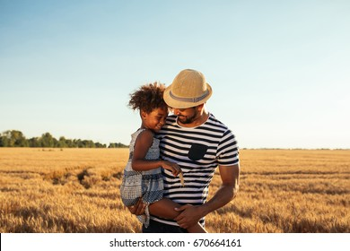 Portrait of an african american father and daughter embracing in the fields.