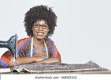 Portrait of an African American female fashion designer with sewing machine and cloth over gray background