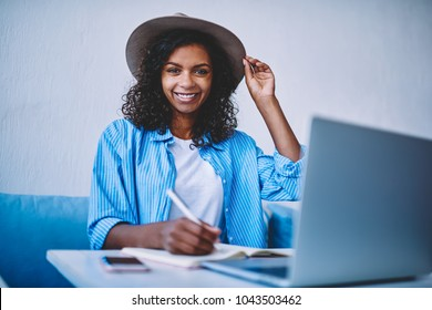 Portrait of african american female freelancer with curly hair and hat making plan of project earning money online,smiling hipster girl looking at camera writing in notepad learning via online courses