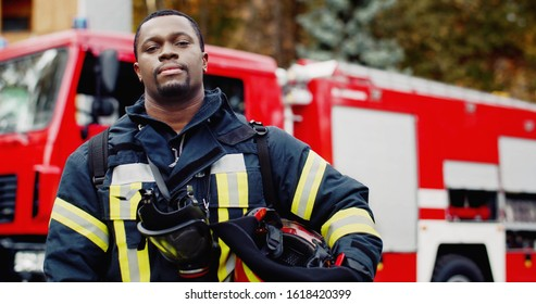 Portrait of african american Firefighter in protective suit with oxygen mask and helmet in hands. Firefighter portrait on duty