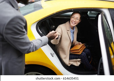 Portrait of African American gentleman helping young smiling Asian woman get out of taxi holding her by hand