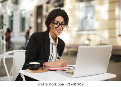 Portrait of African American girl sitting at the table of cafe and writing in her notebook while looking in laptop. Beautiful lady with dark curly hair in jacket working with cup of coffee on table