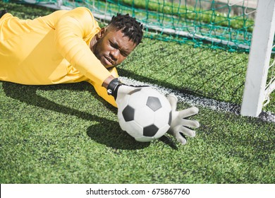 portrait of african american goalkeeper catching ball during soccer match
