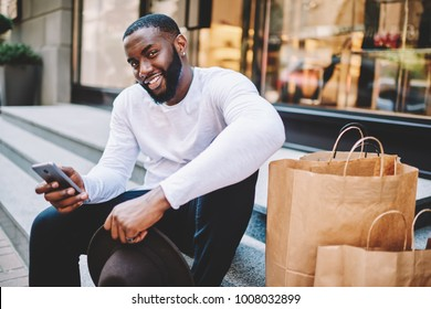Portrait of african american guy wait for feedback from web store service sitting on stairs wait for purchase,smiling dark-skinned man making payment online via mobile satisfied with online shopping
