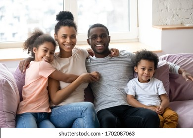 Portrait of african american happy family with two children looking at camera. Cute daughter and son with parents sit on couch in living room. Father and mother enjoying time together with children.