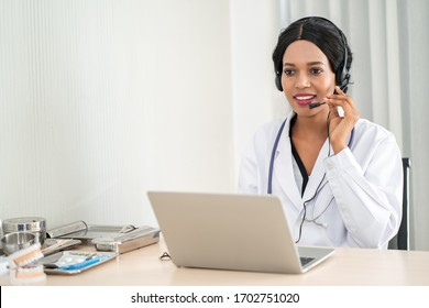 Portrait of african american happy smiling young doctor in headset consulting patient over the phone. Health care call center online concept